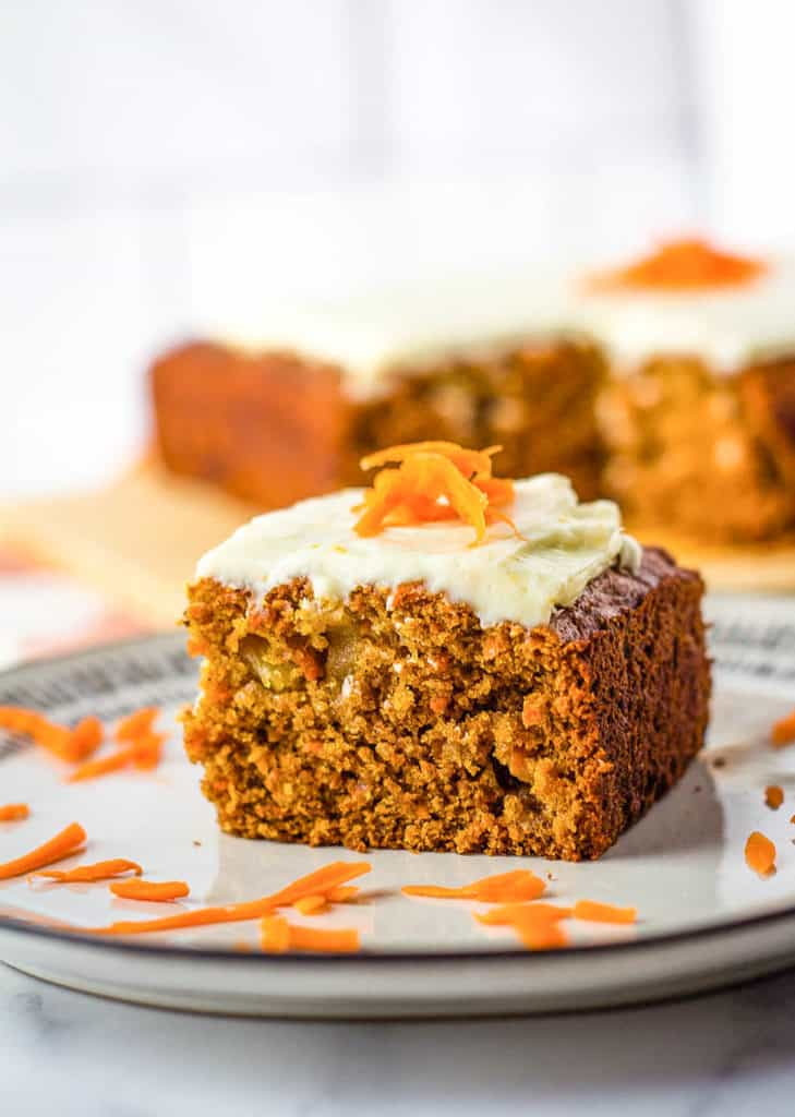 vegan carrot cake with cream cheese frosting on a white plate