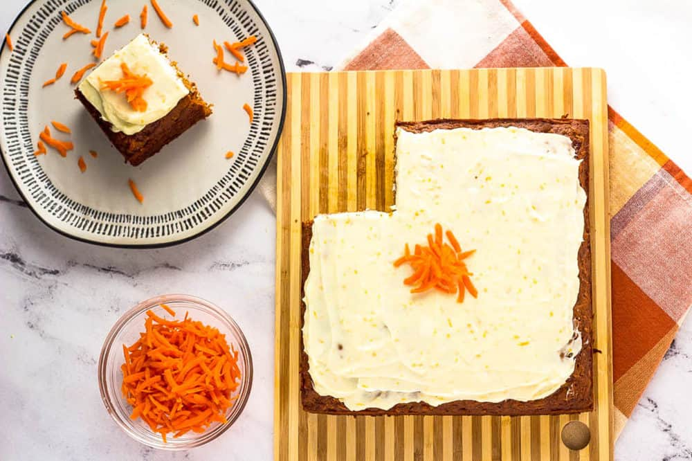 piece of vegan carrot cake with cream cheese frosting on a white plate