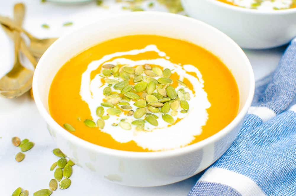 finished soup in a white bowl topped with pumpkin seeds and coconut cream