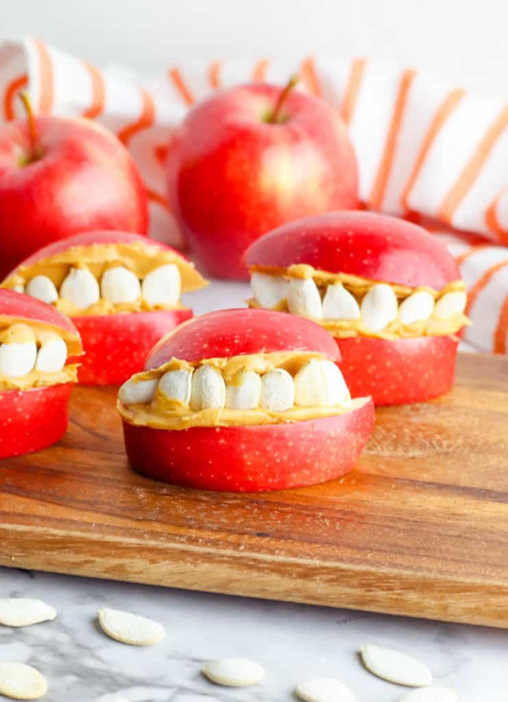 finished funny face halloween apples on a wooden cutting board