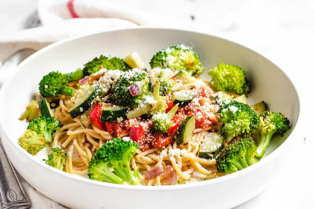 garlic pasta with veggies in a white bowl with parmesan cheese