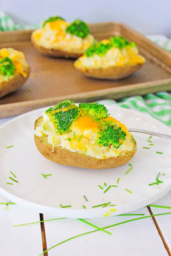 healthy baked potato topped with broccoli and cheese, served on a white plate