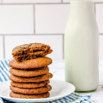 healthy chocolate chip cookies stacked on a cutting board, with one cookie broken for a closeup inside and milk in the background