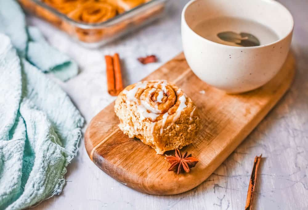 healthy cinnamon rolls, served on a wooden platter with a cup of tea