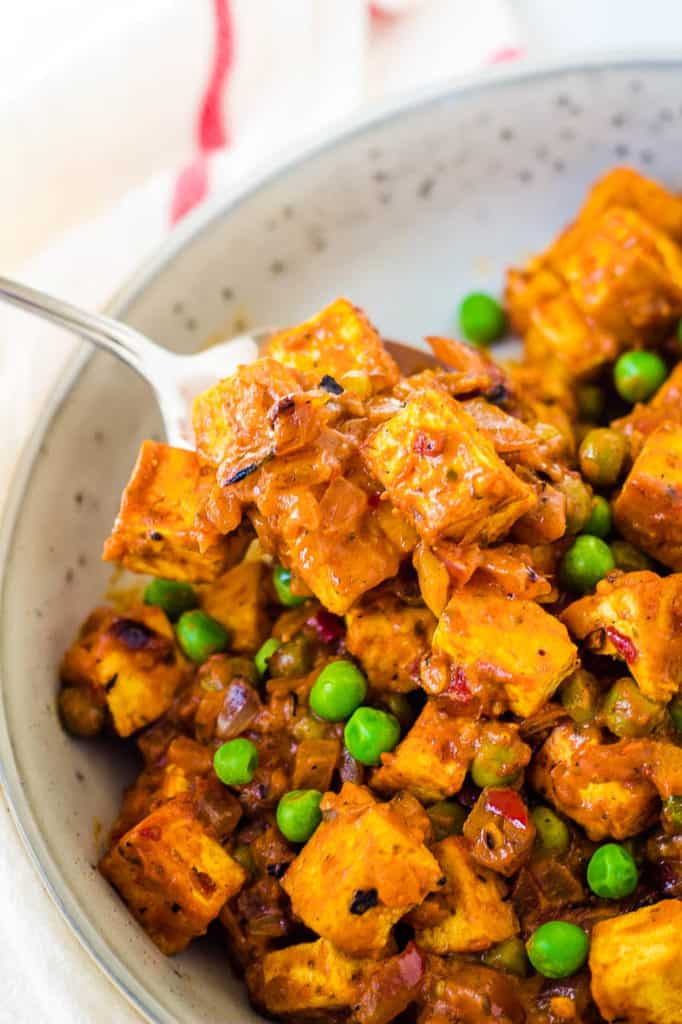 tofu paneer, mattar paneer in a white dish with peas and curry sauce