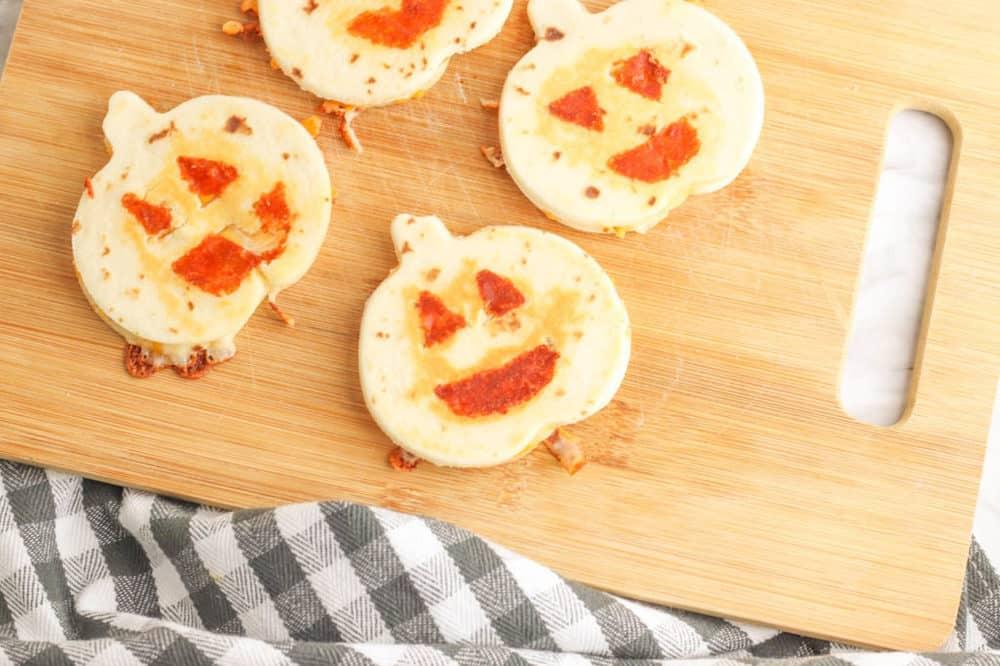 halloween jack-o-lantern pumpkin quesadillas served on a wooden cutting board