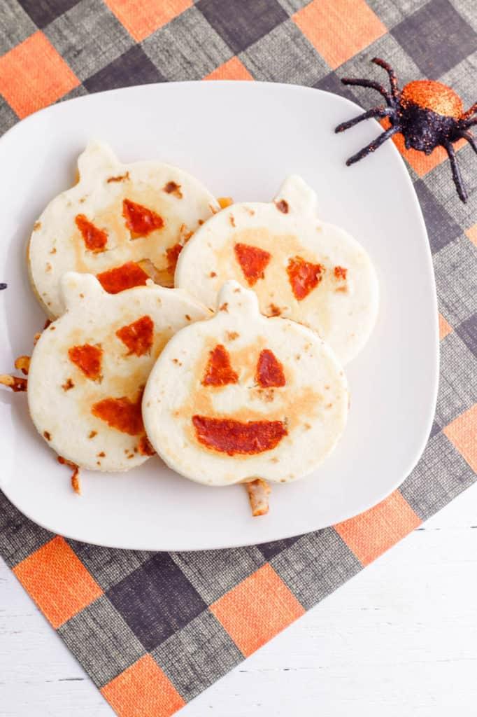 halloween jack-o-lantern pumpkin quesadillas served on a white plate