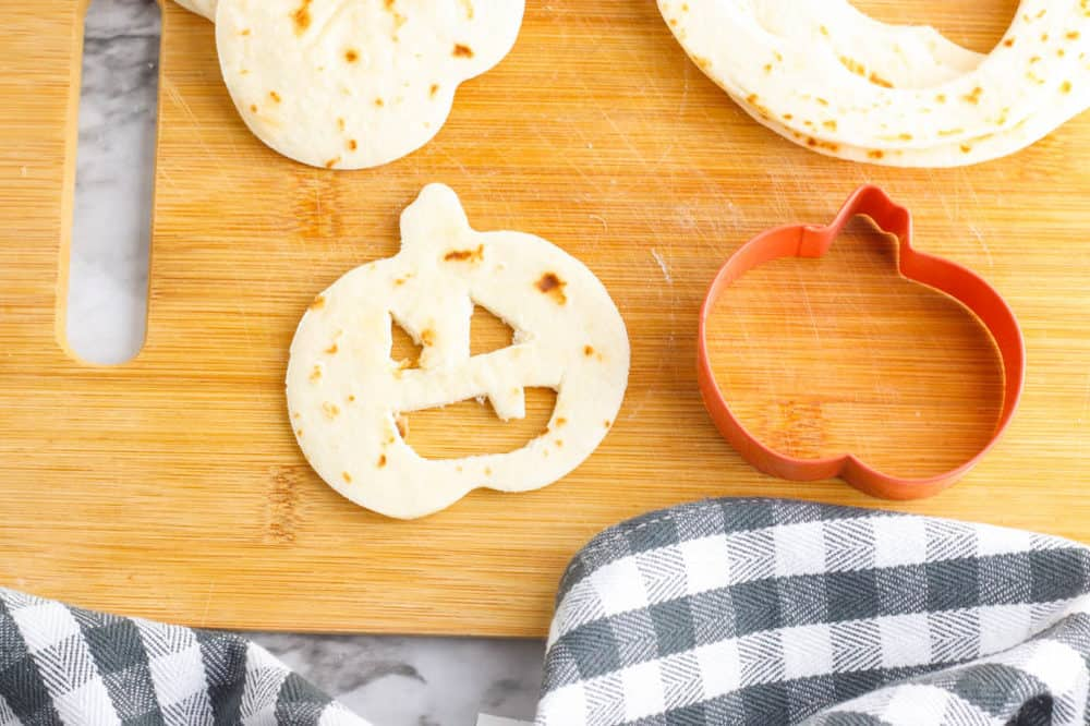 jack o lantern faces cut out of a tortilla on a cutting board