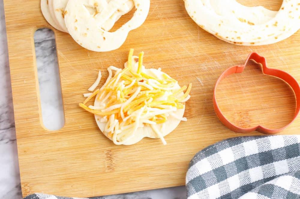 cheese added to quesadilla on cutting board