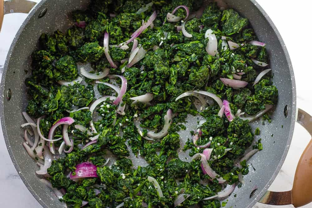 spinach added to onions in a pan