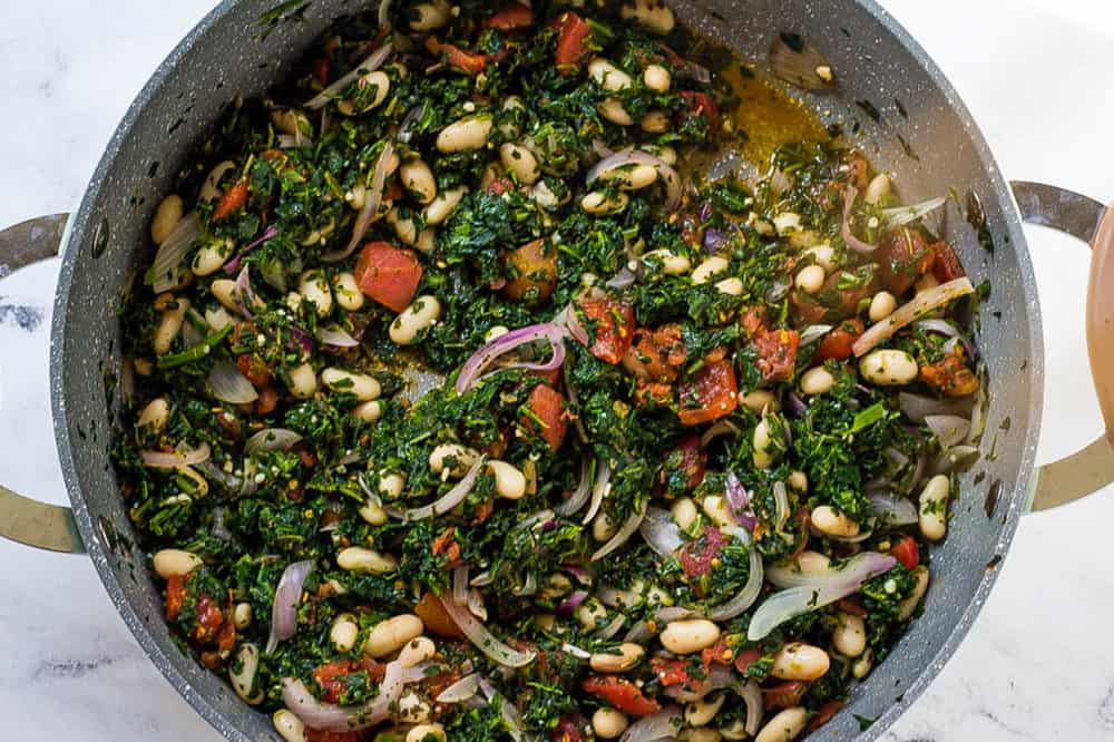 tomatoes and white beans added to spinach and onions in a pan