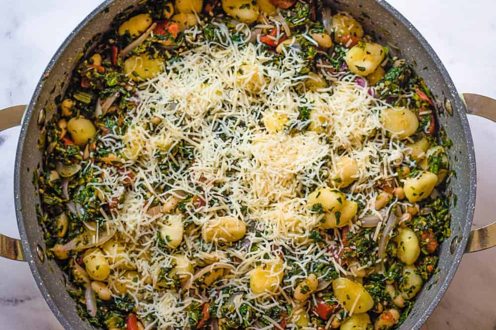 shredded cheese added to gnocchi in a pan