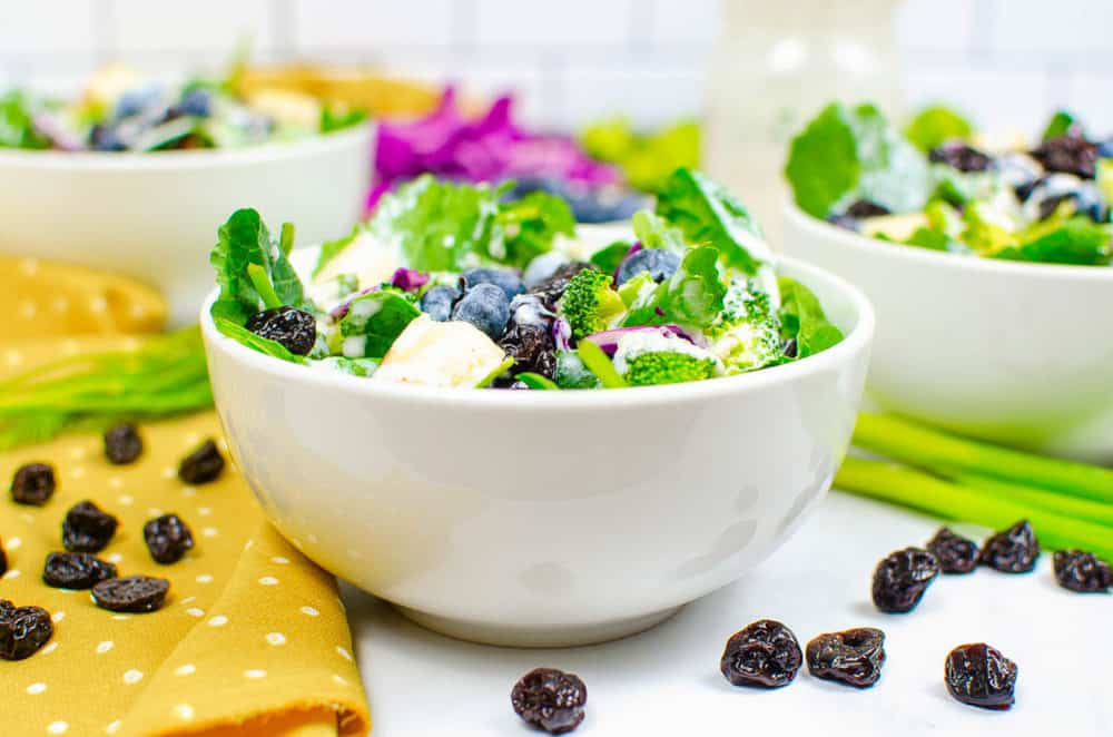 superfood salad served in a white bowl with broccoli, blueberries, sweet Fuji apples, cabbage, spinach, dried cherries, pine nuts, and a healthy ranch dressing