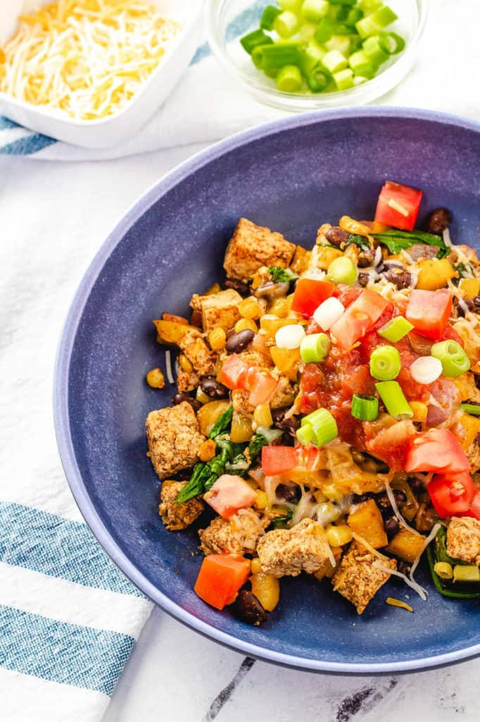 tofu scramble recipe topped with tomatoes, salsa, green onions in a blue bowl
