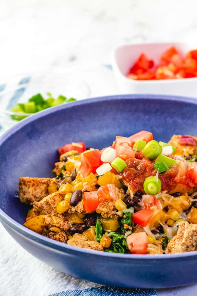 tofu scramble topped with tomatoes, salsa, green onions in a blue bowl