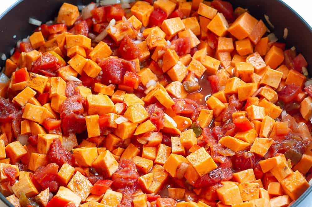sweet potatoes and tomatoes cooking on the stovetop
