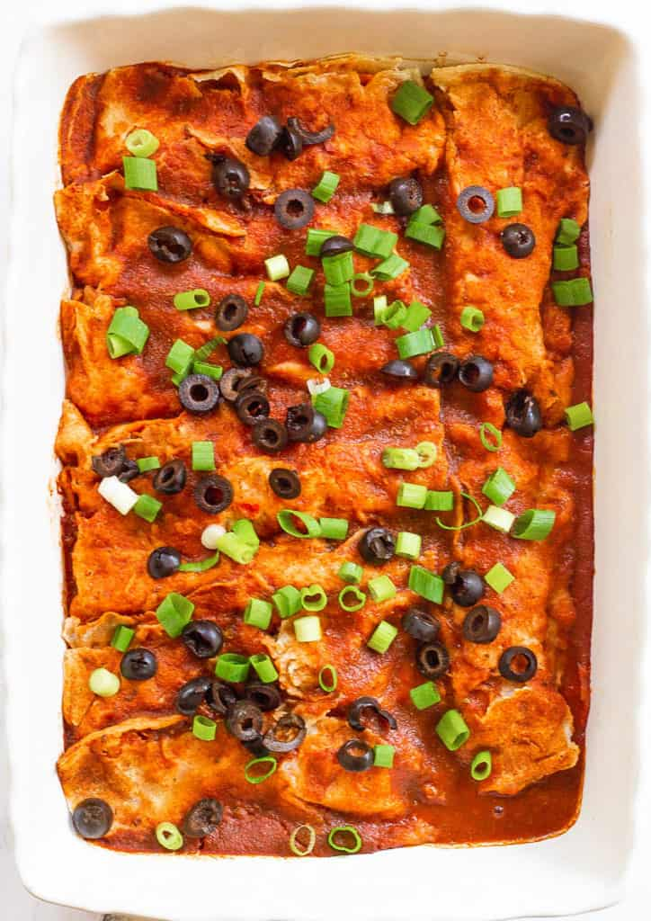 vegan enchiladas, fresh out of the oven, served in a casserole dish and topped with green onions and olives