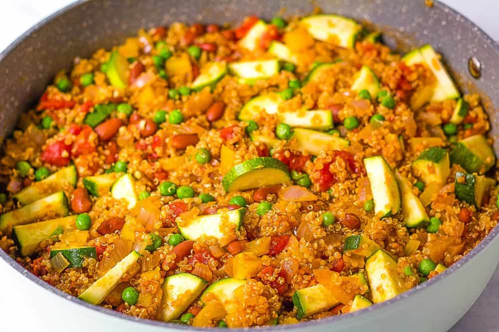 veggies, quinoa and beans cooking in a large pot