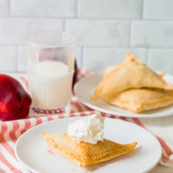 puff pastry apple turnovers topped with homemade whipped cream on a white plate