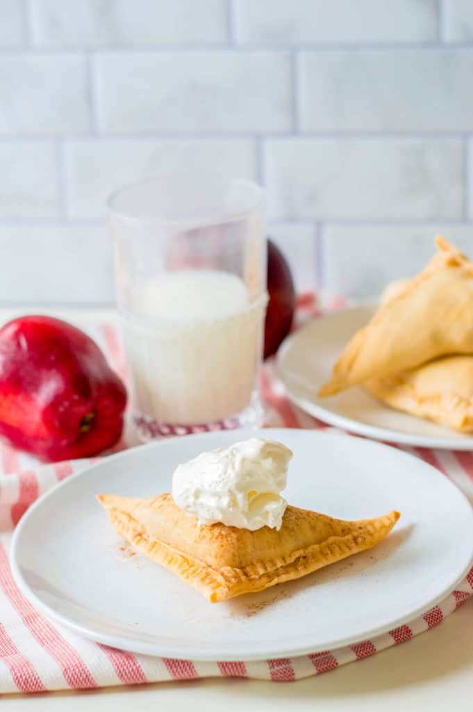 puff pastry apple turnovers topped with homemade whipped cream on a white plate - perfect for vegetarian 4th of July recipes