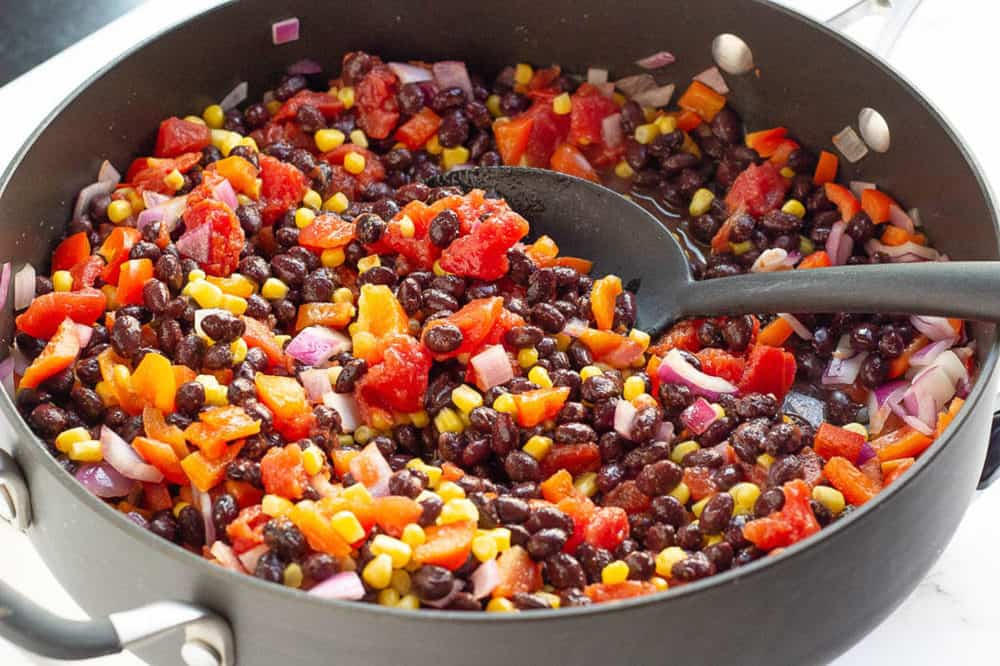 black beans, corn, peppers and onions sauteeing in a pot