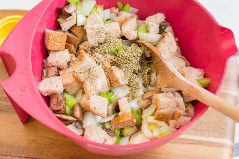 bread and herbs and veggies mixed in a bowl