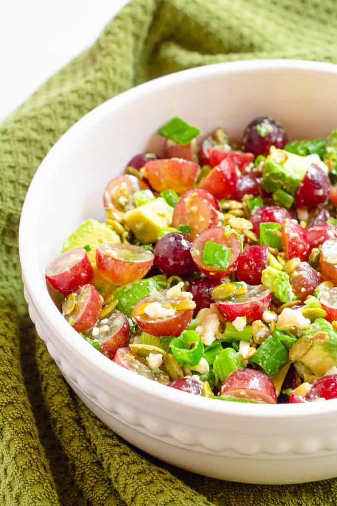recipe for grape salad with avocado and cojita cheese in a white bowl