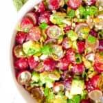 recipe for grape salad with avocado and cojita cheese in a white bowl