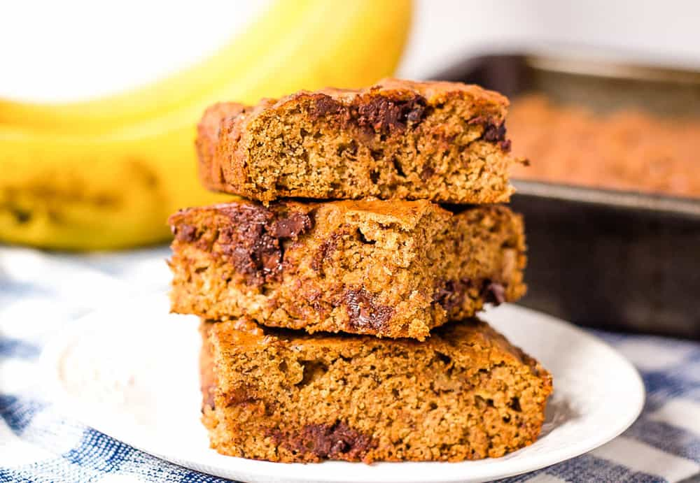 healthy chocolate chip banana bread slices stacked on top of each other on a white plate