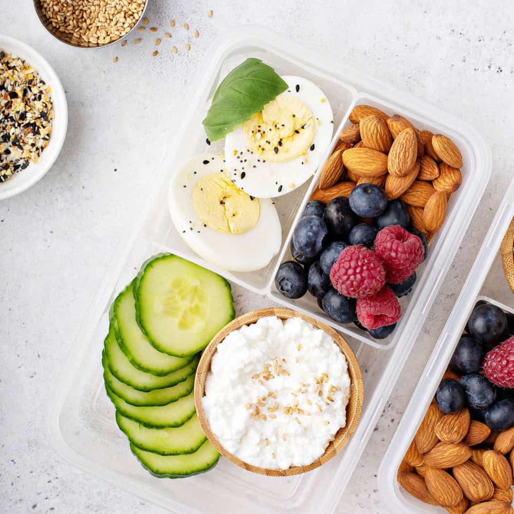 healthy snacks for toddlers - toddler snacks - bento box with hard boiled eggs, nuts, fruit, seeds, cucumbers and cottage cheese