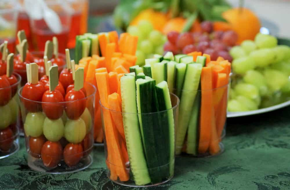 healthy snacks for toddlers - toddler snacks - fresh fruits and vegetables including carrots, cucumbers, tomatoes and grapes on a table at a children's party.