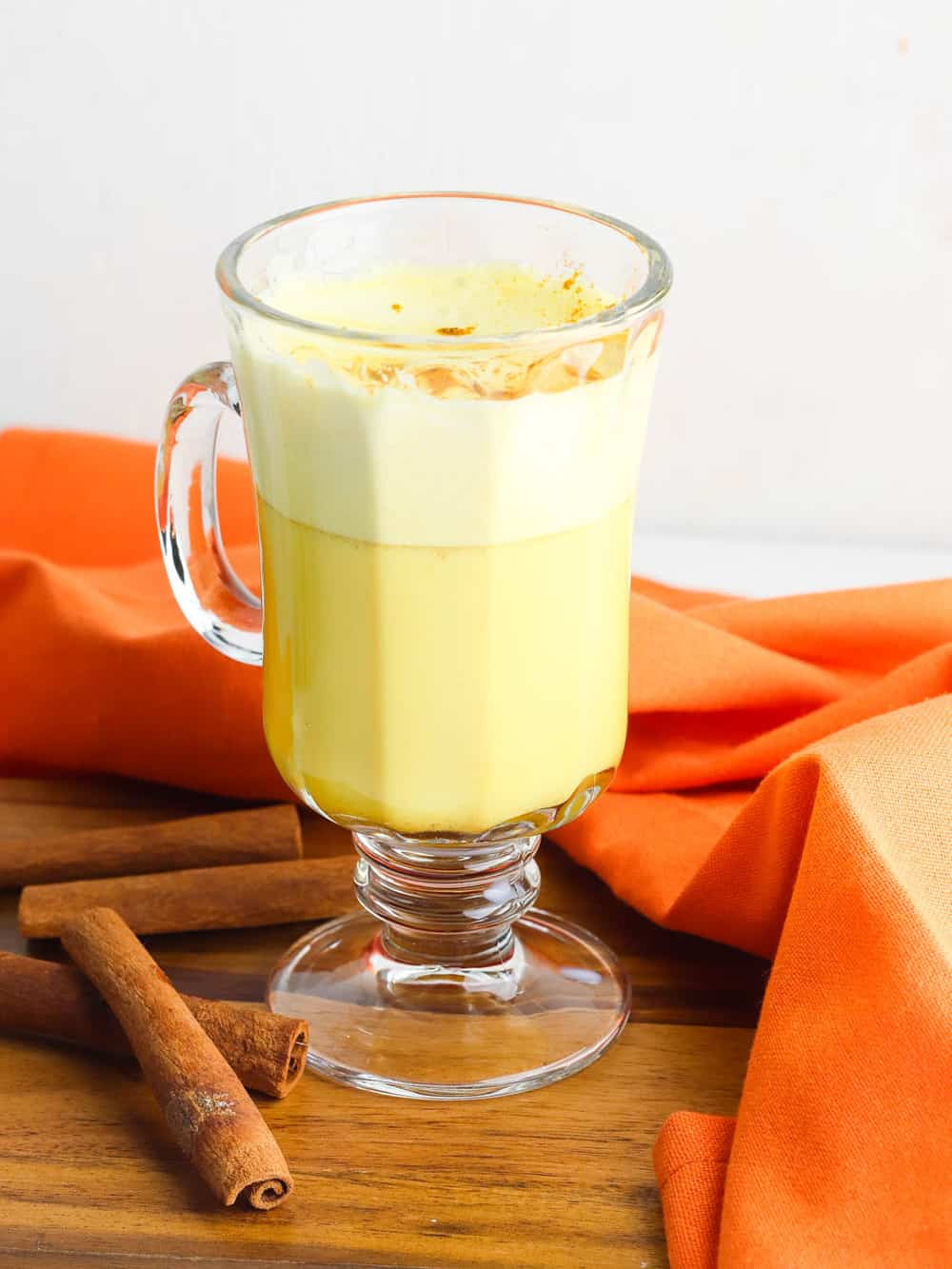 golden milk latte (or turmeric latte) in a glass cup with cinnamon, against an orange background