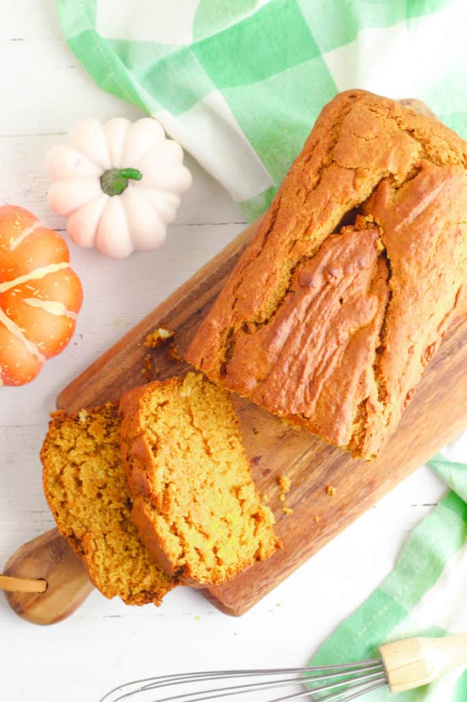 vegan pumpkin bread served on a wooden cutting board and sliced