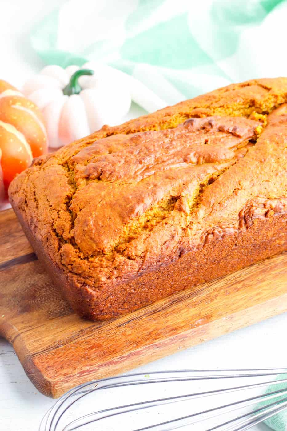 vegan pumpkin bread fresh out of the oven on a wooden cutting board