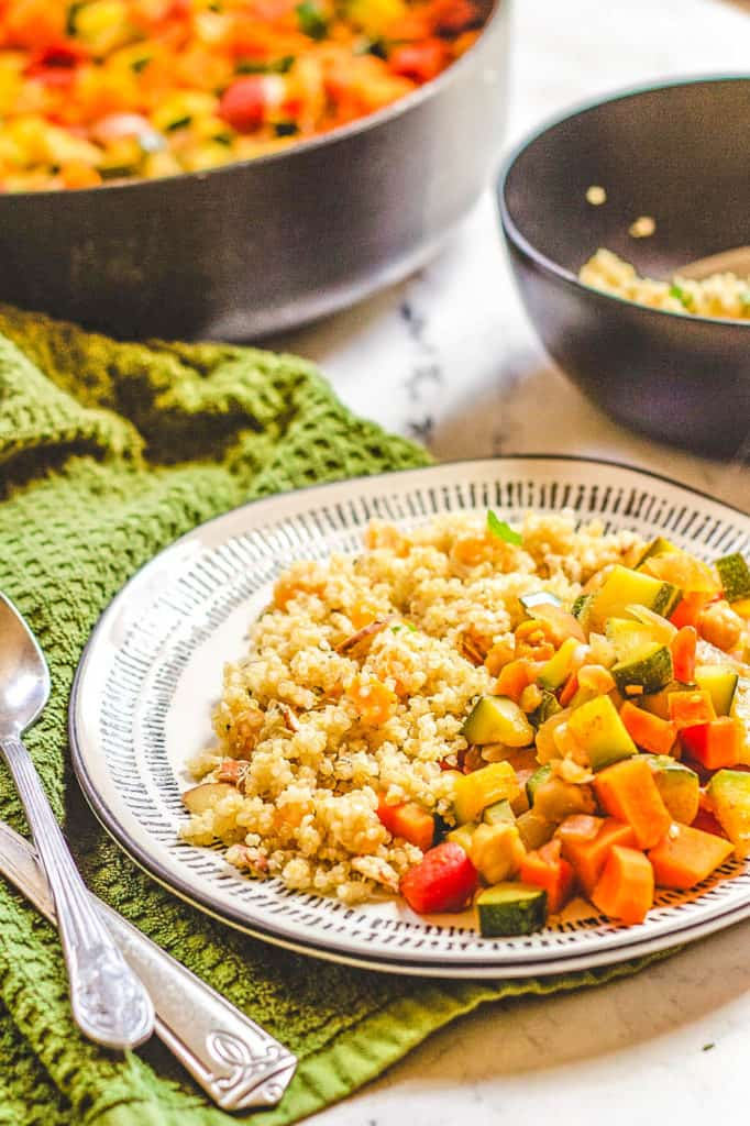 moroccan stew with chickpeas and quinoa couscous served on a white plate - vegetarian gluten free recipes