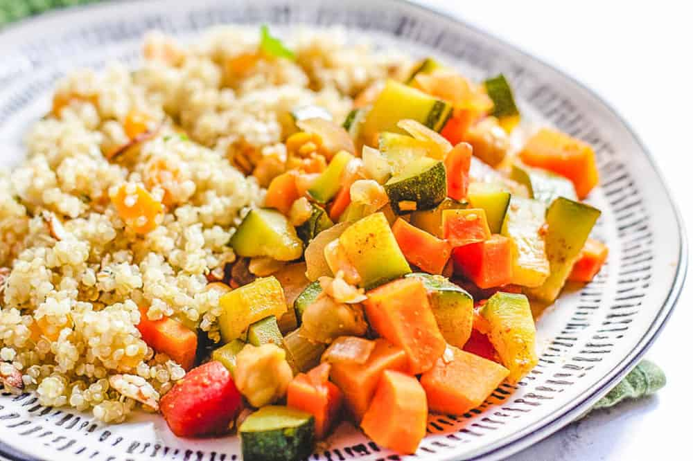 moroccan stew with chickpeas and quinoa couscous served on a white plate