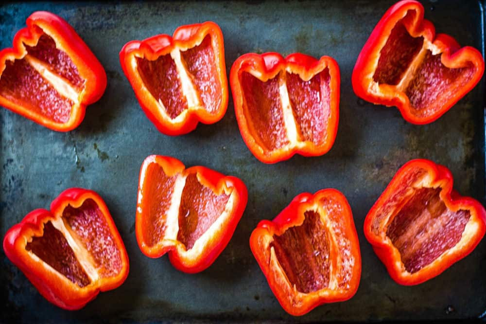 red bell peppers cut in half on a baking sheet