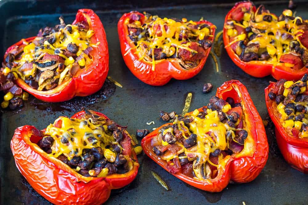 chili stuffed peppers topped with cheese, fresh out of the oven (on a baking sheet)