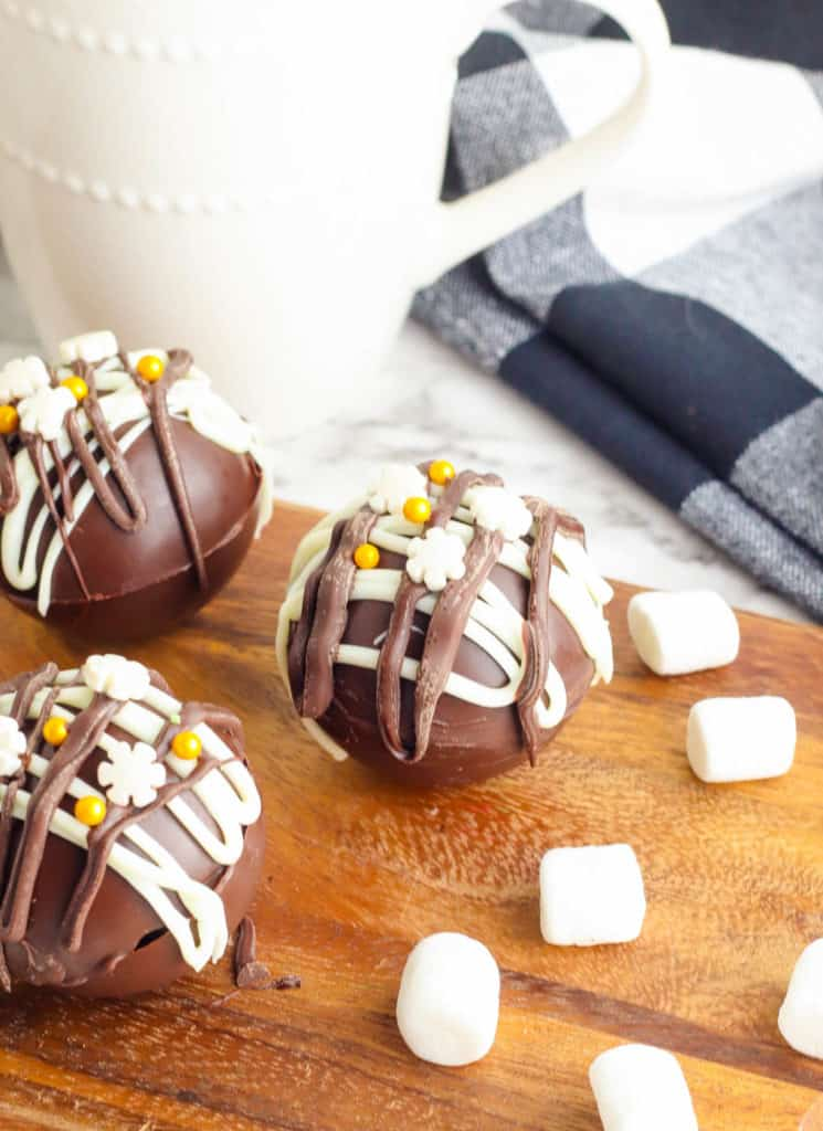 hot chocolate bombs with marshmallows on a cutting board