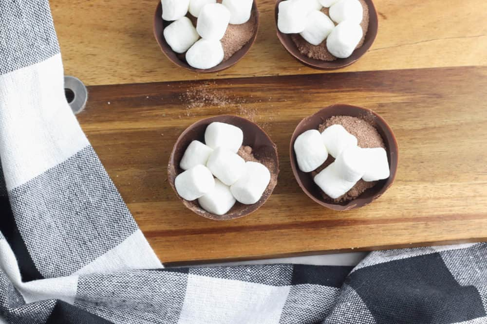 marshmallows and cocoa powder in half shell of chocolate