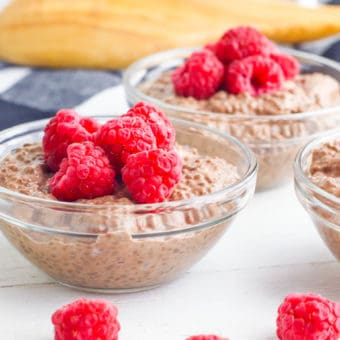 vegan chocolate mousse topped with raspberries served in a glass bowl