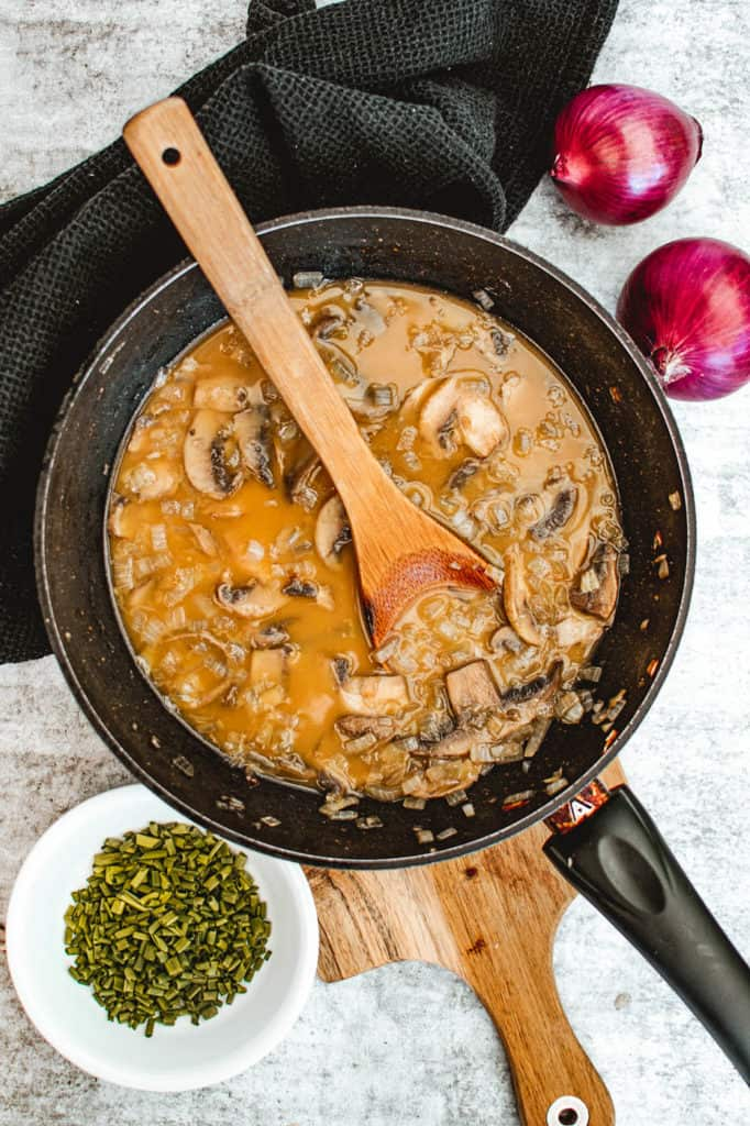 mushrooms and broth sauteeing in a pan