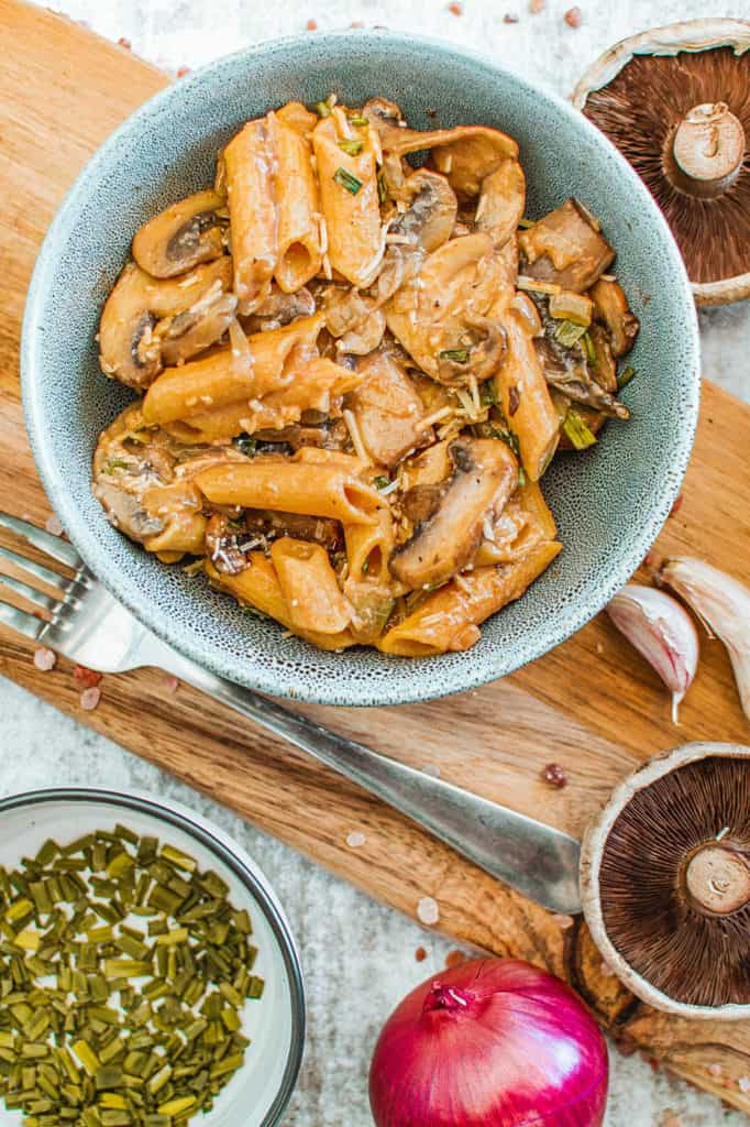 vegan mushroom stroganoff served in a blue bowl with garnishes on the side, top view