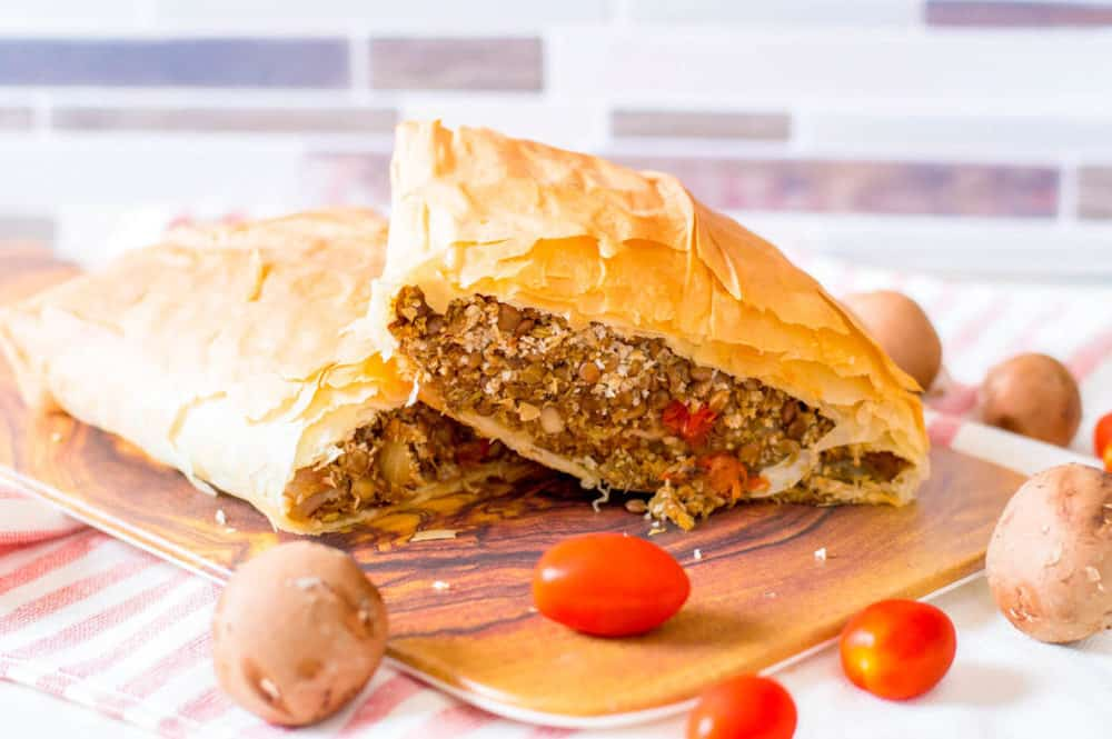 vegan wellington with lentils and mushrooms, served on a wooden cutting board