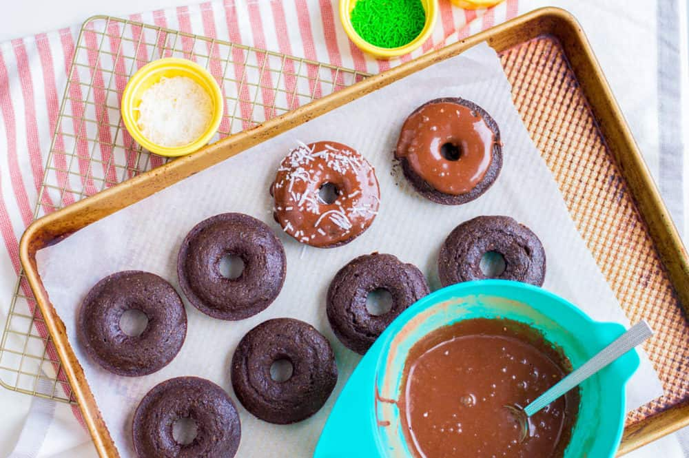chocolate doughnuts being iced