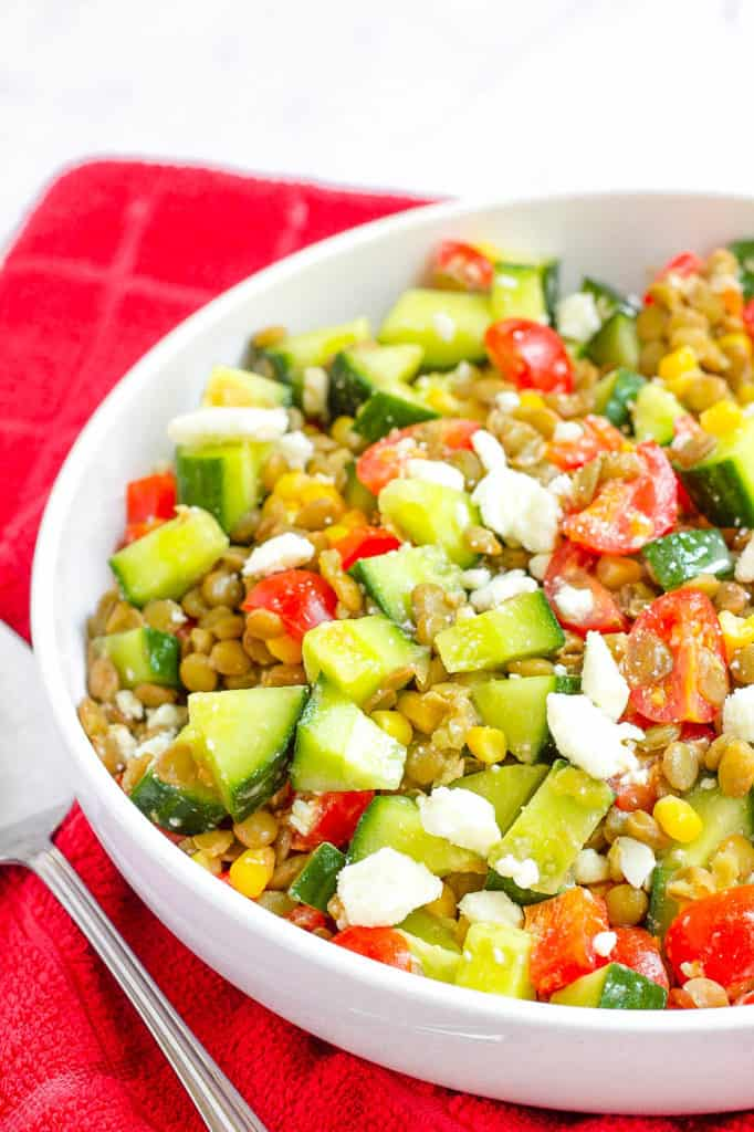 feta salad with lentils, cucumbers, tomatoes, corn in a bowl
