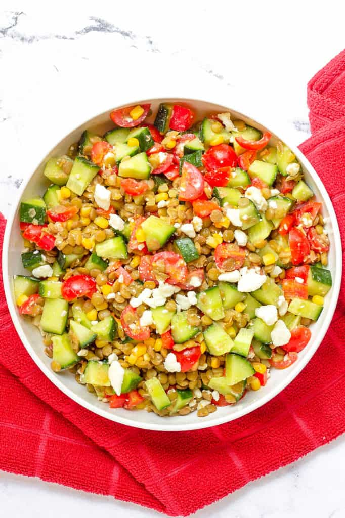 feta salad with lentils, cucumbers, tomatoes, corn in a white bowl