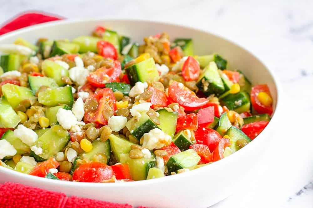 feta salad with lentils, cucumbers, tomatoes, corn in a bowl - healthy side dishes