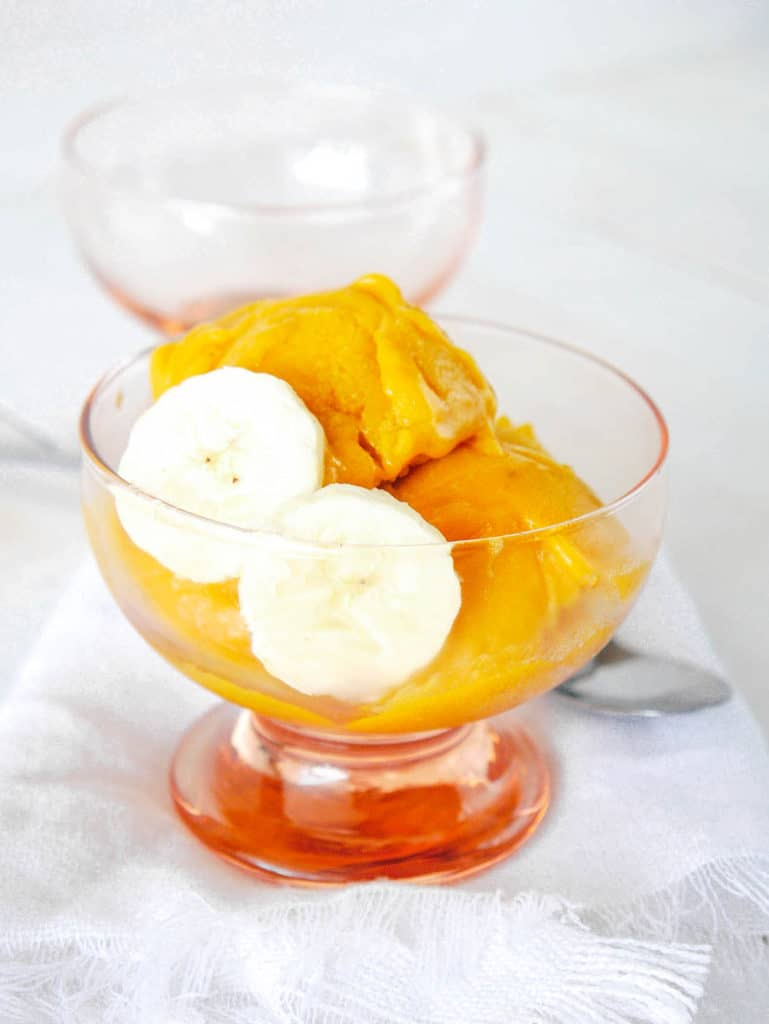 mango nice cream in a glass container with sliced bananas