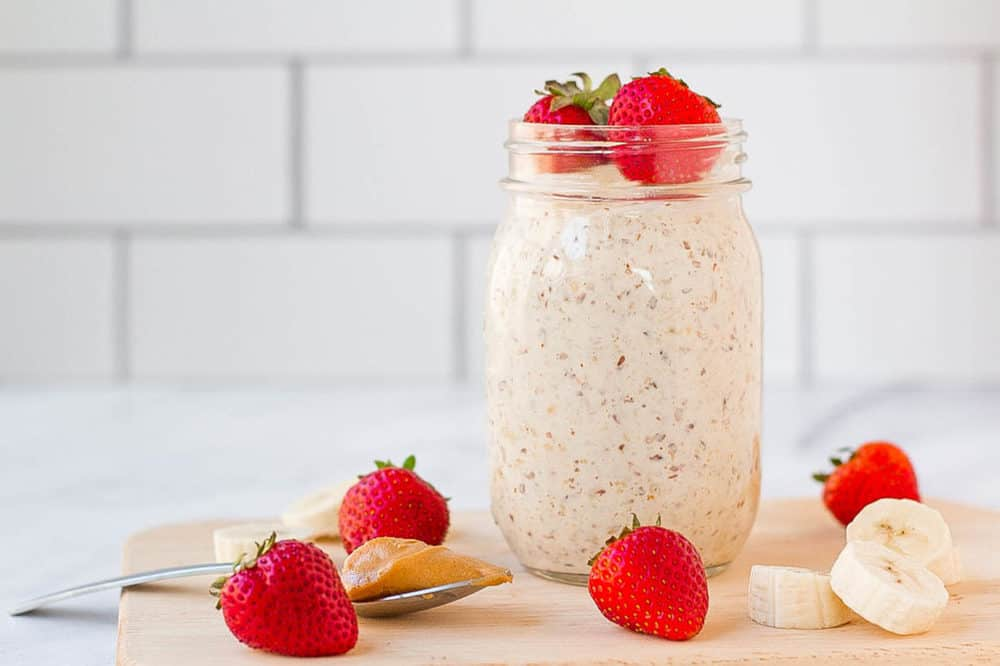 peanut butter overnight oats in a mason jar with strawberries and bananas